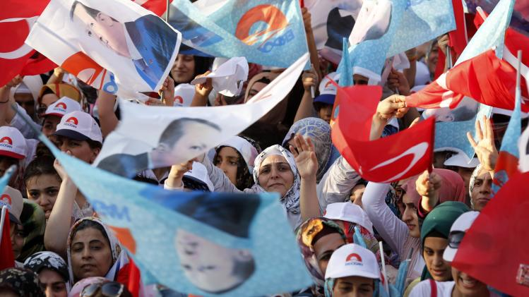 Supporters of Turkey's Prime Minister and presidential candidate Tayyip Erdogan wave flags and shout slogans during an election rally in Diyarbakir