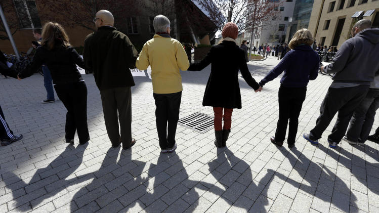 People link hands to form a human chain from a makeshift memorial for fallen MIT police officer Sean Collier to a campus police station at the Massachusetts Institute of Technology in Cambridge, Mass., Monday, April 22, 2013. A moment of silence for victims of the marathon bombings was also observed during the event. Collier was fatally shot on the MIT campus Thursday, April 18, 2013. Authorities allege that Boston Marathon bombing suspects Tamerlan and Dzhokhar Tsarnaev were responsible. (AP Photo/Steven Senne)
