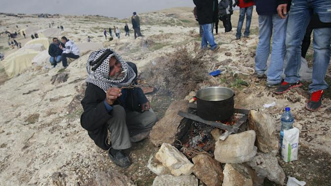 A Palestinian Bedouin men Lit cigar in the new 'outpost ' of Bab al-Shams (Gate of the Sun) in an area known as E1, near Jerusalem, Friday, Jan 11, 2013. Palestinian activists pitched tents in the West Bank on Friday to protest Israeli plans to build a large Jewish settlement on a key route through the territory. The E-1 settlement would block east Jerusalem from its West Bank hinterland — both territories captured by Israel during the 1967 Mideast war. (AP Photo/Majdi Mohammed)