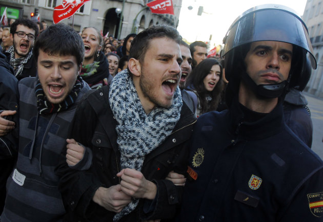 A protestor shout at  the police during a general strike in Madrid, Spain, Wednesday, Nov. 14, 2012. Spain's main trade unions stage a general strike, coinciding with similar work stoppages in Portuga