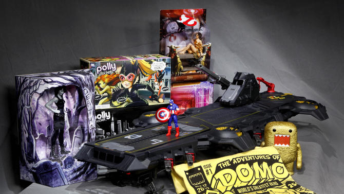 """In this July 5, 2012 photo, the Marvel Universe S.H.I.E.L.D. Super Helicarrier, at center with a Captain America figure on the foredeck, is seen with, from left background, a DC Comics Vertigo Death figurine, the Polly Pocket DC Comics Villain set, and a Dana as Zuul """"Ghostbusters"""" figure, all special-issue Comic-Con 2012 collectibles, shown in Los Angeles. The annual four-day Comic-Con festival runs July 12-15, 2012, in San Diego. (AP Photo/Reed Saxon)"""