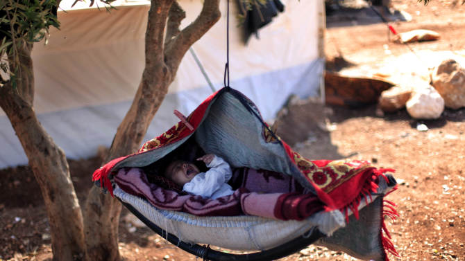 FILE - In this Monday, Nov. 5, 2012 file photo, a Syrian baby cries as he lays on a swing attached to a tree at a camp for displaced families, in the Syrian village of Atmeh, near the Turkish border with Syria. Most of the displaced people in the tent camp rising near this village on the Syrian-Turkish border are children. All have fled the violence of Syria's civil war further south. Many have seen violence themselves, some have lost relatives, and most have trouble sleeping and panic when they hear loud noises or airplanes, their parents say. The Atmeh camp was born of necessity about three months ago, say the local rebels who run the place, distributing tents and food aid provided by a smattering of aid organizations.(AP Photo/ Khalil Hamra, File)