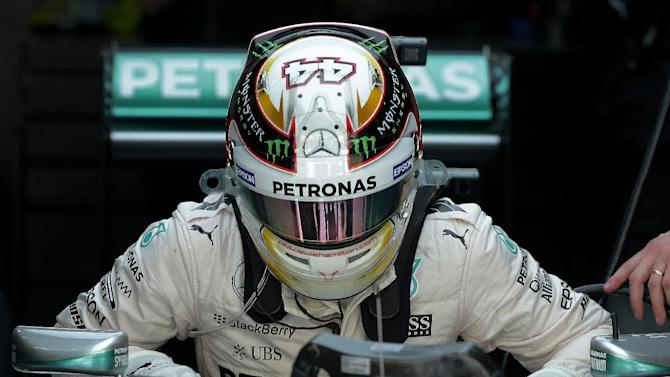 Mercedes driver Lewis Hamilton of Britain gets up from his car after after the second practice session for the Malaysian Formula One Grand Prix at Sepang International Circuit in Sepang, Malaysia Friday, March 27, 2015. (AP Photo/Andy Wong)