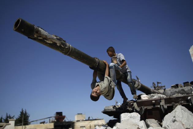 A  boy looks back while he and another boy play on a Syrian military tank, destroyed during fighting with the Rebels, in the Syrian town of Azaz, on the outskirts of Aleppo, Sunday, Sept. 2, 2012. (AP