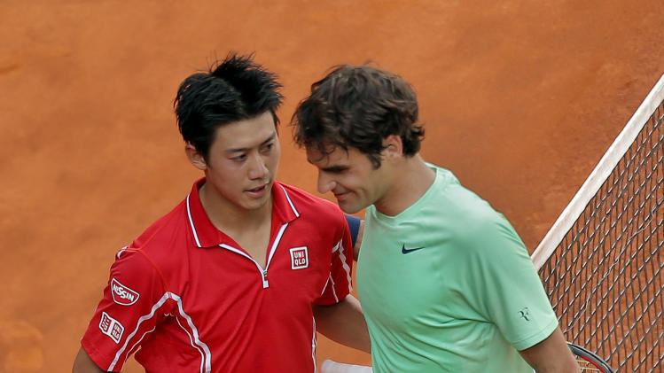Kei Nishikori from Japan, left, hugs Roger Federer from Switzerland, right, as he celebrates his victory at the Madrid Open tennis tournament, in Madrid, Thursday, May 9, 2013. (AP Photo/Andres Kudacki)