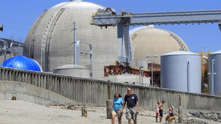 FILE - In this June 30, 2011 file photo, beach-goers walk on the sand near the San Onofre nuclear power plant in San Clemente,  Calif. A report commissioned by an environmental group warned Tuesday, May 15, 2012 that running California's San Onofre nuclear plant at reduced power would not resolve problems with badly worn tubing that have kept its twin reactors offline for more than three months, and might make it worse. (AP Photo, Lenny Ignelzi, File)