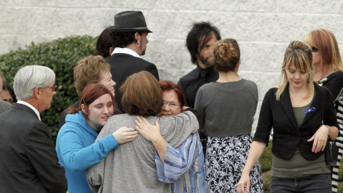 People hug after attending a public viewing for Autumn Pasquale at Our Lady of Lourdes Church, in Glassboro, N.J. on Saturday Oct. 27, 2012.  Two teenage brothers were charged Tuesday with murdering Pasquale, 12, who had been missing since the weekend, prompting a frantic search until her body was found in a recycling bin.. (AP Photo/Joseph Kaczmarek)