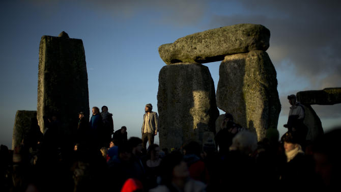 """People soak up the sun after its rise at the ancient stone circle of Stonehenge, in southern England, as access to the site is given to druids, New Age followers and members of the public on the annual Winter Solstice, Friday, Dec. 21, 2012.  Doomsday hour is here and so still are we.  According to legend, the ancient Mayans' long-count calendar ends at midnight Thursday, ushering in the end of the world. Didn't happen.  """"This is not the end of the world. This is the beginning of the new world,"""" Star Johnsen-Moser, an American seer, said at a gathering of hundreds of spiritualists at a convention center in the Yucatan city of Merida, an hour and a half from the Mayan ruins at Chichen Itza. (AP Photo/Matt Dunham)"""