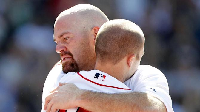 Boston Red Sox's Kevin Youkilis, left, hugs teammate Dustin Pedroia as Youklis comes off the field after hitting a triple and being replaced with a pinch runner in the seventh inning of a baseball game against the Atlanta Braves in Boston, Sunday, June 24, 2012. (AP Photo/Michael Dwyer)