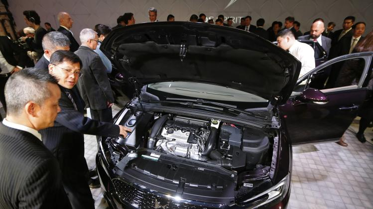 Chinese journalists and guests inspect the new Citroen DS 5LS sedan automobile, which will be constructed and sold exclusively in China, at an event in Paris