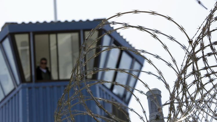 FILE - In this Aug. 17, 2011 file photo, concertina wire and a guard tower are seen at Pelican Bay State Prison near Crescent City, Calif. Gov. Jerry Brown is criticizing attorneys representing inmates and court-appointed masters and experts who he says have a financial incentive to drag out lawsuits against the state.  One of the lawsuits involves crowding in state prisons. (AP Photo/Rich Pedroncelli, File)