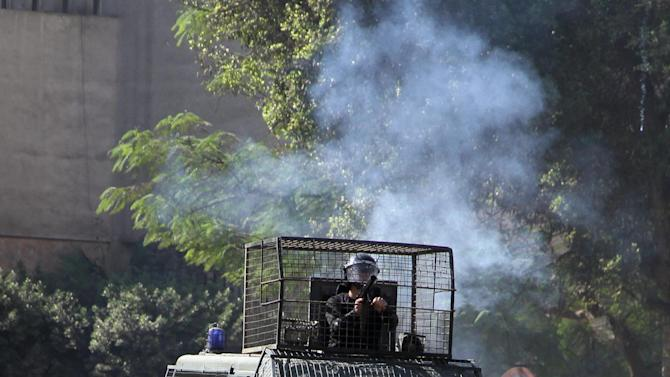Egyptian security forces clash with protesters near Tahrir Square in Cairo, Egypt, Sunday, Nov. 25, 2012. Supporters and opponents of Egypt's president grow more entrenched in their potentially destabilizing battle over the Islamist leader's move to give himself near absolute powers, with neither side appearing willing to back down. (AP Photo/Ahmed Gomaa)