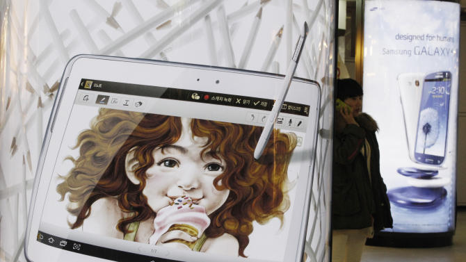 A woman uses her smartphone between a billboard of Samsung Electronics' Galaxy S III and Galaxy Note 10.1, left, at a subway station in Seoul, South Korea, Friday, Jan. 25, 2013. Samsung Electronics Co. said quarterly profit soared 76 percent, boosted by the popularity of its Galaxy smartphones, which outsold the iPhone for a fourth straight quarter. But the company said Friday it expects earnings to decline during the current quarter because of seasonally low demand for consumer electronics. (AP Photo/Ahn Young-joon)