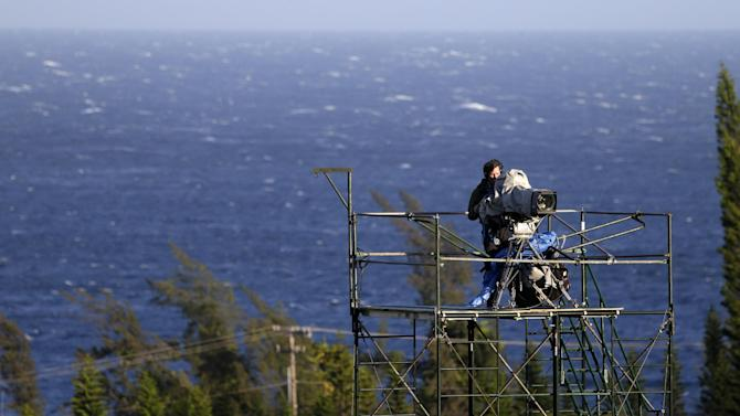Trees bend in the wind and whitecaps form on the Pacific ocean behind a broadcast camera operator atop a platform before the first round at the Tournament of Champions PGA golf tournament on Sunday, Jan. 6, 2013. in Kapalua, Hawaii. Play was to have started two days earlier but was delayed because of rain and high winds. (AP Photo/Elaine Thompson)