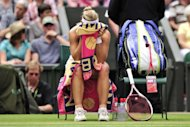 Germany's Angelique Kerber buries her head in her towel during a break between games in her women's singles semi-final defeat to Poland's Agnieszka Radwanska on day 10 of the 2012 Wimbledon Championships tennis tournament at the All England Tennis Club in Wimbledon, on July 5. Radwanska won 6-3, 6-4