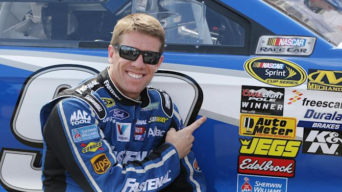 Driver Carl Edwards points to the pole-winner sticker he placed on his car after qualifying for Sunday's NASCAR Sprint Cup series auto race at Michigan International Speedway Friday, June 14, 2013, in Brooklyn, Mich. (AP Photo/Carlos Osorio)