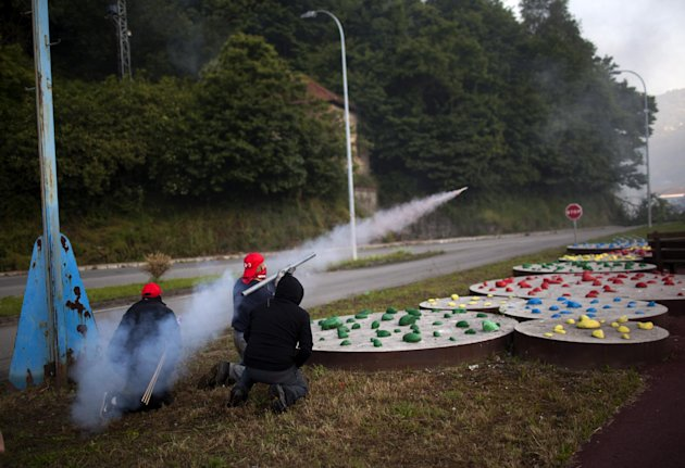 Miners fire handmade rockets at riot police officers as they defend their position near the mine &quot;El Soton&quot; during clashes in El Entrego near Oviedo, Spain, Friday, June 15, 2012. Strikes, road blockades, and mine sit-ins continue as 8,000 mineworkers at over 40 coal mines in northern Spain continue their protests against government action to cut coal subsidies. (AP Photo/Emilio Morenatti)