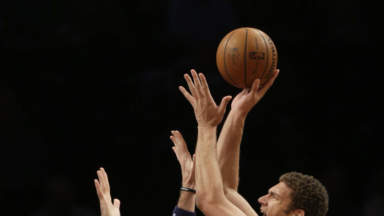 Brooklyn Nets' Brook Lopez, right, shoots over Washington Wizards' Marcin Gortat during the first half of an NBA basketball game Wednesday, Dec. 18, 2013, in New York. (AP Photo/Seth Wenig)