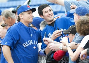 Toronto Blue Jays manager John Gibbons, left, poses for a photograph with a fan before the Jays take on the Minnesota Twins during MLB Grapefruit League baseball action Dunedin, Fla., on Tuesday, Feb. 26, 2013. THE CANADIAN PRESS/Nathan Denette