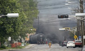 Smoke rises from railway cars that were carrying crude…