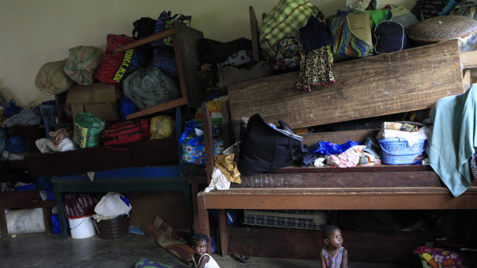FILE In this May 30, 2011 file photo, Ivorian toddlers play alongside piled belongings in a classroom at the Catholic Mission, then serving as a camp for tens of thousands of area residents who fled the post-election violence, in Duekoue, in western Ivory Coast. Two years after the nation's deadly postelection standoff, only supporters of former president Laurent Gbagbo have been charged for crimes, although it is widely acknowledged that abuses were committed on both sides. Meanwhile, violence continues to be inflicted with impunity on some Gbagbo supporters, preventing reconciliation in the country, according to a report issued Tuesday, Feb. 26, 2013 by Amnesty International. (AP Photo/Rebecca Blackwell, File)