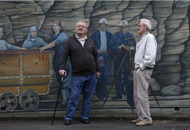 Joseph Leder, 77,  a retired iron ore miner at the Algrange mine, talks with retired colleague Niessen in front of a wall fresco representing the work of iron mineworkers next to their homes in Algran
