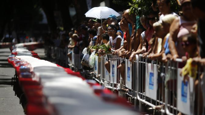 People look at a 450-metre long cake that was prepared as part of celebrations to mark the 450th anniversary of the city of Rio de Janeiro