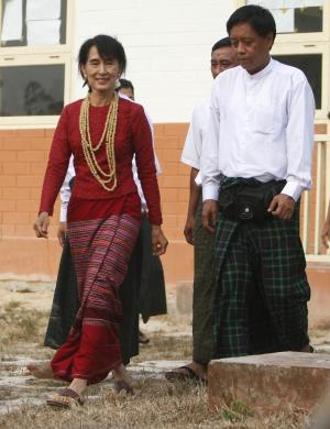 Myanmar's pro-democracy leader Aung San Suu Kyi, left, walks out of a polling station on the outskirts of Yangon, Myanmar, Sunday, April 1, 2012. Myanmar held a landmark election Sunday that was expected to send Suu Kyi into parliament for her first public office since launching her decades-long struggle against the military-dominated government. (AP Photo)