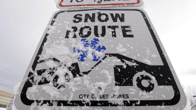 Snow clings to a Snow Route sign on a city street, Thursday, Dec. 20, 2012, in Des Moines, Iowa. The first widespread snowstorm of the season began a slow crawl across the Midwest on Thursday with some areas receiving as much as 15 inches of snow. (AP Photo/Charlie Neibergall)