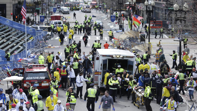 FILE - In this April 15, 2013 file photo, medical workers aid injured people at the finish line of the 2013 Boston Marathon following a bomb explosion in Boston, Monday, April 15, 2013.  In addition to Tamerlan Tsarnaev, who died after a gunfight with police, and his brother, Dzhokhar Tsarnaev, who was captured and lies in a hospital prison, three more suspects in the bombings were taken into custody, Boston police said Wednesday, May 1, 2013.  (AP Photo/Charles Krupa, File)