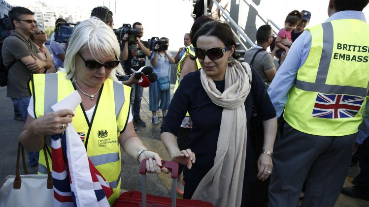 "A staff member of the British embassy in Athens assists an evacuee after her disembarkation from the Greek frigate ""Salamis"" in Athens"