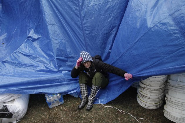 Gina Kohm tries to keep a tarp from blowing away which covers a pile of donated supplies at an aid station in the New Dorp section of Staten Island, New York, Wednesday, Nov. 7, 2012.  Residents of Ne