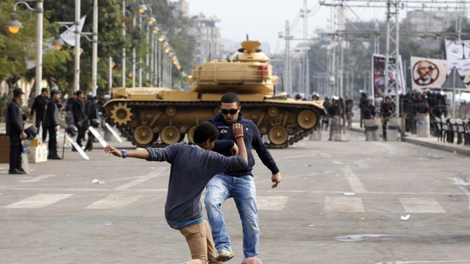Protesters play with a ball in front of a tank securing the area around the presidential palace in Cairo, Egypt, Friday, Dec. 14, 2012. Opposing sides in Egypt's political crisis were staging rival rallies on Friday, the final day before voting starts on a contentious draft constitution that has plunged the country into turmoil and deeply divided the nation. (AP Photo/Petr David Josek)