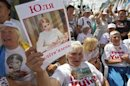A supporter of jailed former Ukrainian PM and opposition leader Tymoshenko holds a portrait of her during a rally in central Kiev