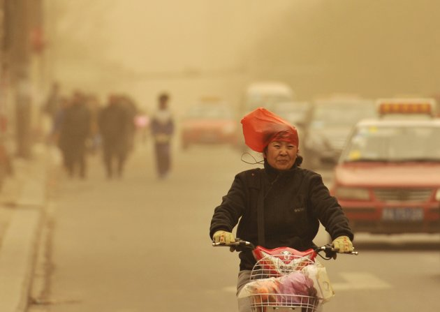 A woman wearing a plastic bag over her head rides along a street against wind on a hazy day in Taiyuan