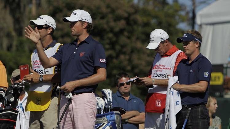 Webb Simpson, second from left, and Luke Donald, right, of England, prepare to tee off on their first hole during the second round of the Children's Miracle Network Classic golf tournament, Friday, Oct. 21, 2011, in Lake Buena Vista, Fla. (AP Photo/John Raoux)