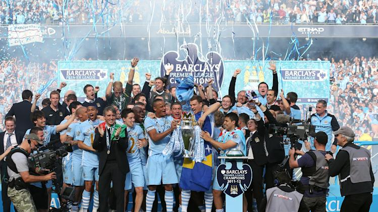 Manchester City team members celebrate with the English Premier League trophy after their 3-2 win over Queens Park Rangers at The Etihad Stadium, Manchester, England, Sunday May 13, 2012. (AP Photo/Jon Super)
