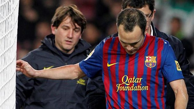 Barcelona's Andres Iniesta (R) leaves the pitch injured companied by doctor Ricard Pruna during their Spanish King's Cup soccer match against Hospitalet at Camp Nou stadium in Barcelona