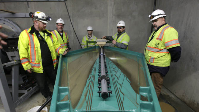 In this photo taken Thursday, Dec. 13, 2012, Matt Collins, chief operating officer of the Sutter Gold Mining Co., left, watches as Allen Smith, second from left, Brain Herfel, third  from left, Ted Chapman fouth from left, and Wayne Murphy, right,  calibrate the water flow of a gravity table at the company's newly constructed mill near Sutter Creek, Calif. The gravity table uses technology  similar to those used by gold rush-era miners who used pans to separate gold from surrounding materials.    The company, which has begun mining adjacent to the historic Comet-Lincoln ore zones,  announced Monday, Dec. 17, 2012, that it poured its first gold as it prepared to begin the first large scale Sierra Nevada underground  gold mining in a half century. (AP Photo/Rich Pedroncelli)