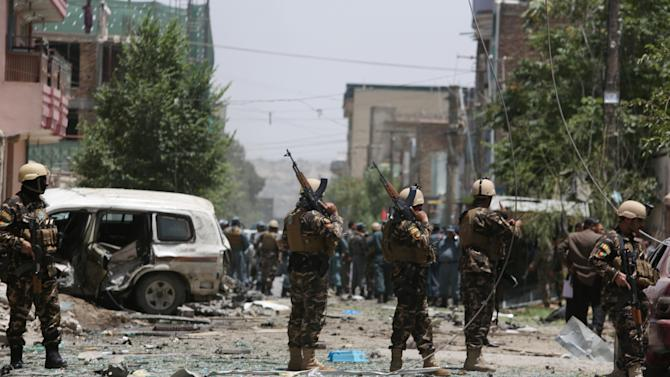 Afghan security personnel inspect the site of a suicide attack that targeted a NATO convoy in Kabul, Afghanistan, Tuesday, July 7, 2015. An Afghan official said the attack by a suicide car bomber in the capital, Kabul, wounded at least two people.  (AP Photo/Rahmat Gul)