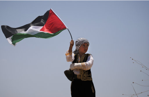 A Palestinian boy holding a Palestinian flag celebrates last weekend's moving of a portion of Israel's West Bank separation barrier in the town of Bilin, near Ramallah, Friday, July 1, 2011. The local residents on Friday began to construct buildings in the newly accessible land. (AP Photo/Majdi Mohammed)
