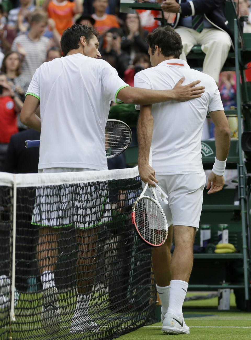 Sergiy Stakhovsky of Ukraine, left, speaks with Roger Federer of Switzerland after he defeated him in their Men's second round singles match at the All England Lawn Tennis Championships in Wimbledon, London, Wednesday, June 26, 2013. (AP Photo/Alastair Grant)