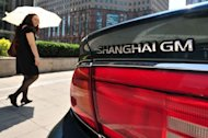 A woman walks past a General Motor's vehicle in Beijing
