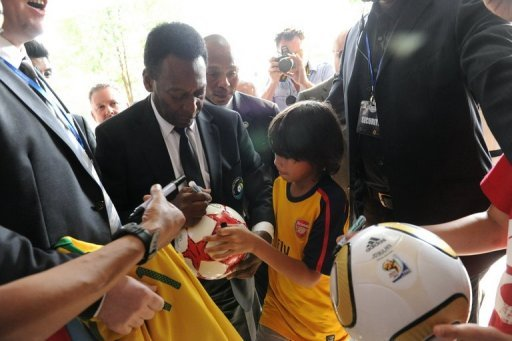 Retired Brazilian footballer Pele (C), signs autographs in Singapore