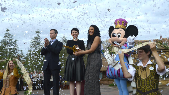 Walt Disney World Parks and Resorts Chairman Tom Staggs, left, and the character Mickey Mouse, right, applaud as actress Ginnifer Goodwin, second from left, and singer Jordin Sparks cut the ceremonial ribbon for the New Fantasyland attraction at the Walt Disney World Resort's Magic Kingdom theme park in Lake Buena Vista, Fla., Thursday, Dec. 6, 2012. The new attraction is the largest expansion at the Magic Kingdom.(AP Photo/Phelan M. Ebenhack)