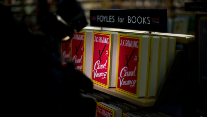 "A light from a video camera shines on copies of the ""The Casual Vacancy"" by author J.K. Rowling displayed on shelves at a book store in London, Thursday, Sept. 27, 2012.  British bookshops are opening their doors early as Harry Potter author J.K. Rowling launches her long anticipated first book for adults.  Publishers have tried to keep details of the book under wraps ahead of its launch Thursday, but ""The Casual Vacancy"" has gotten early buzz about references to sex and drugs that might be a tad mature for the youngest ""Potter"" fans.  (AP Photo/Matt Dunham)"