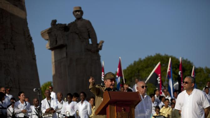 Cuba's President Raul Castro speaks at a podium as Vice President Jose Ramon Machado, second from right, stands by during celebrations marking Revolution Day in Guantanamo, Cuba, Thursday, July 26, 2012. Cuba marks the 59th anniversary of the July 26, 1953 rebel attack led by Fidel and Raul Castro on the Moncada military barracks. The attack is considered the beginning of the revolution that culminated with dictator Fulgencio Batista's ouster. (AP Photo/Ramon Espinosa)