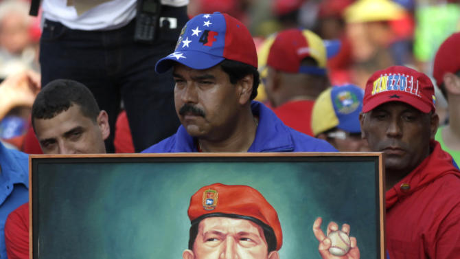 Venezuela's acting President Nicolas Maduro holds up a painting of late President Hugo Chavez during a campaign rally in Catia La Mar, Venezuela, Tuesday, April 9, 2013. Maduro, the hand-picked successor of late President Hugo Chavez, is running for president against opposition candidate Henrique Capriles in the presidential election set for Sunday, April 14. (AP Photo/Ariana Cubillos)