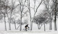 A lone cyclist navigates the bike path through a snow storm at Chicago&#39;s North Ave. beach Thursday, Dec. 27, 2012. A muted version of the deadly winter storm that has killed more than a dozen across the eastern half of the country reached the Northeast on Thursday, limiting most of its wrath to travel headaches as Christmas revelers tried to return home. (AP Photo/Charles Rex Arbogast)