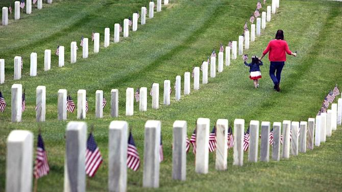 Katie Mcgaha, right, walks with Madelyn Andrews, of Woodland Hills, Calif., while placing flags at headstones in remembrance of Memorial Day, Monday, May 25, 2015, at The Los Angeles National Cemetery in Los Angeles. (AP Photo/Richard Vogel)